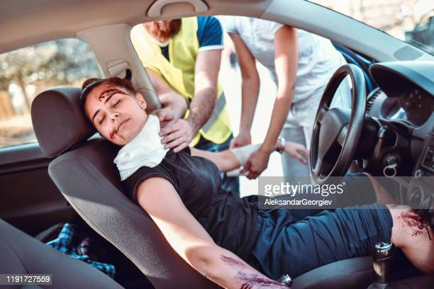 paramedics trying to stop female from bleeding out after car crash - gory car accident photos stock pictures, royalty-free photos & images