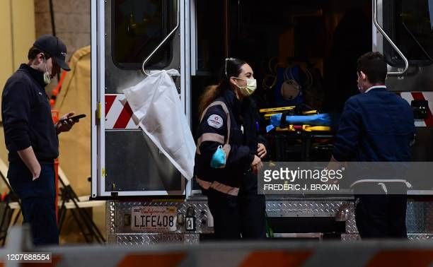 Paramedics wearing facemasks work behind an ambulance at the Garfield Medical Center in Monterey Park California on March 19 2020 All residents of...
