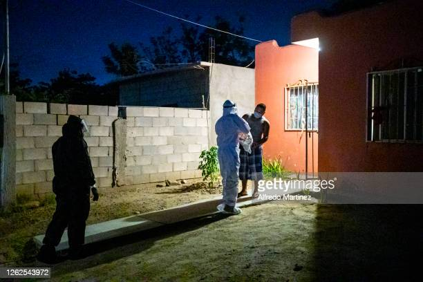 Paramedics wearing PPE from the Calafia group deliver a food pantry to a man on July 28, 2020 in La Paz, Mexico. Many Mexican States remain in orange...