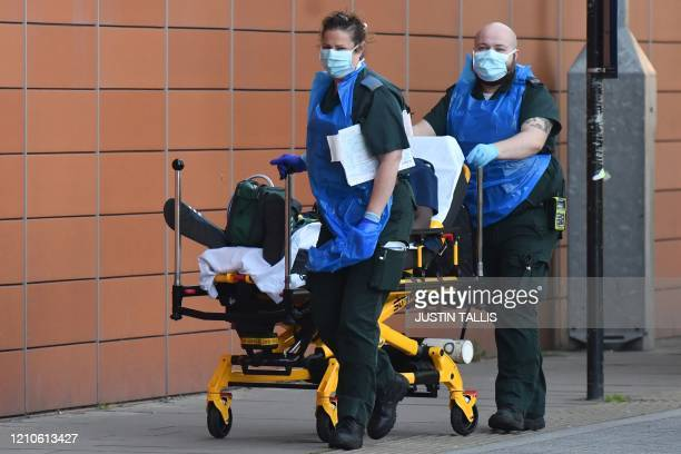 Paramedics wearing PPE including face masks aprons and gloves as a precautionary measure against COVID19 wheel a patient into The Royal London...