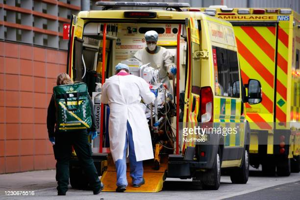 Paramedics wearing PPE wheel a patient from an ambulance outside the emergency department of the Royal London Hospital in London, England, on January...