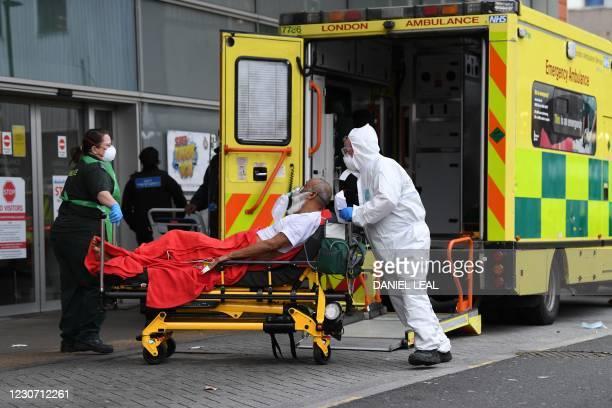 Paramedics wheel a patient from an ambulance into the Royal London Hospital in east London on January 21, 2021. - Britain's coronavirus mortality...