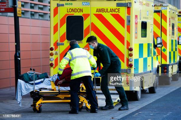 Paramedics wheel a patient into the emergency department of the Royal London Hospital in London, England, on January 25, 2021. Across the UK, deaths...