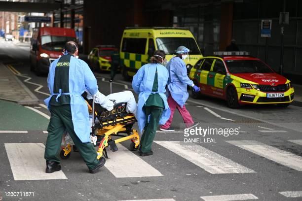 Paramedics wheel a patient outside the Royal London Hospital in east London on January 21, 2021. - Britain's coronavirus mortality rate has risen...