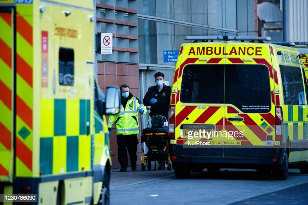 Paramedics wheel a stretcher past ambulances outside the emergency department of the Royal London Hospital in London, England, on January 25, 2021....