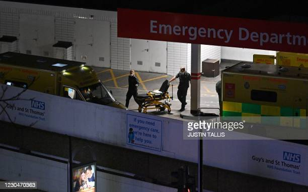 Paramedics wheel a trolley bed back to an ambulance outside the Accident and Emergency department at Guy's and St Thomas' Hospital in central London...
