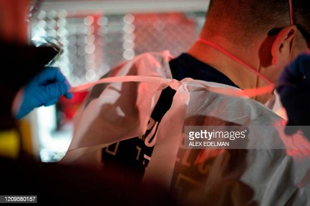 Paramedics with the Anne Arundel County Fire Department put on a gowns while responding to a 911 call for a suspected COVID19 patient on April 9 2020...