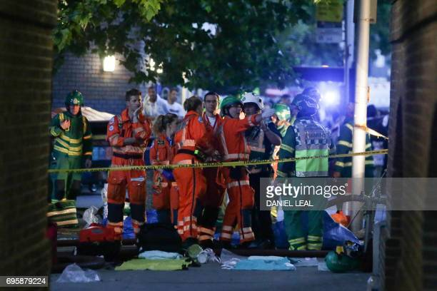 Paramedics working at the scene ned to a huge fire at Grenfell Tower in west London on June 14 2017 The massive fire ripped through the 27storey...