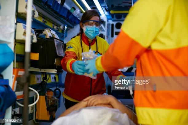 Paramedics working inside an ambulance and wearing protective gear.