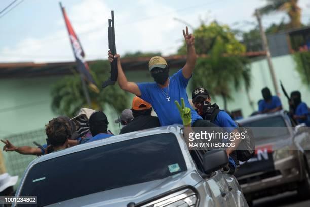 TOPSHOT Paramilitaries flash the V sign from a truck at Monimbo neighborhood in Masaya Nicaragua on July 18 following clashes with antigovernment...