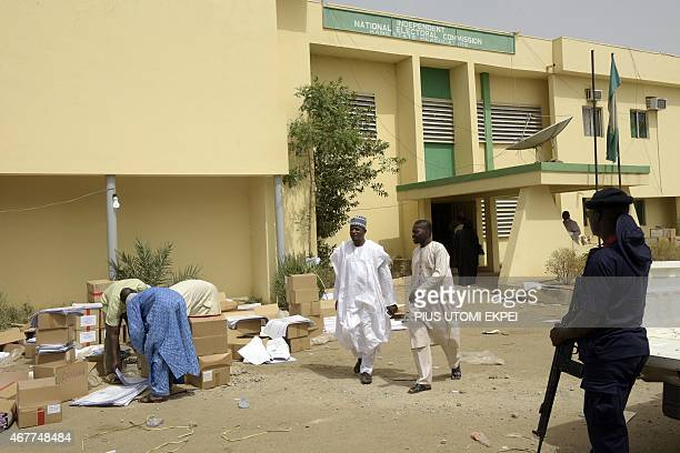 A paramilitary officer stand as workers gather materials for the election at the secretariat of Independent National Electoral Commission in Kano on...