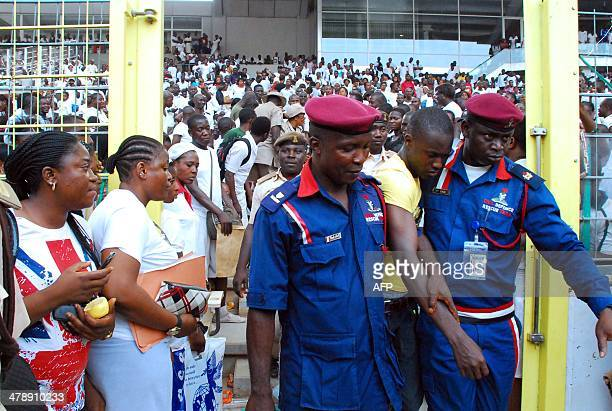 Paramilitary officers carry an injured man to an ambulance after a stampede in Abuja National Stadium where thousands of jobseekers came to apply for...