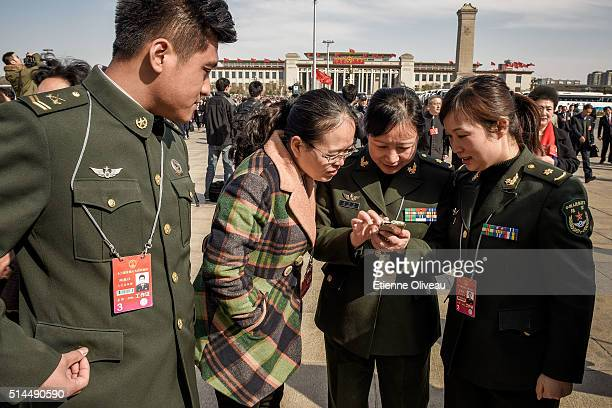 Paramilitary officers check photos on their phone before the Second plenary session of the National People's Congress on March 9, 2016 in Beijing,...