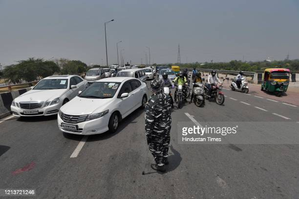 A paramilitary personnel manages traffic during lockdown near Sarai Kale Khan on May 18 2020 in New Delhi India
