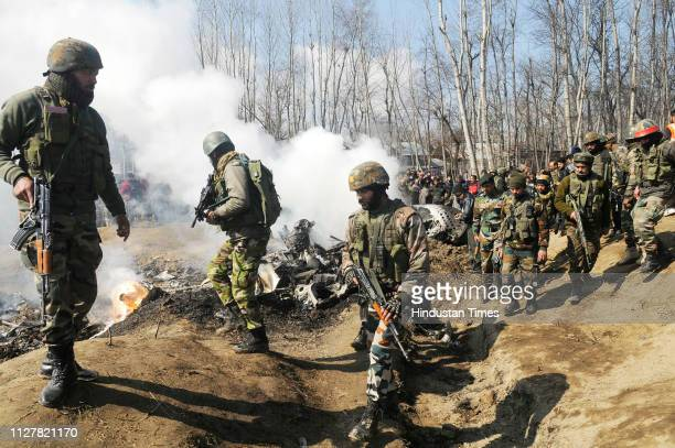 Paramilitary personnel stand near the wreckage of an Indian Air Force helicopter after it crashed on February 27 2019 in Budgam IndiaTwo pilots were...