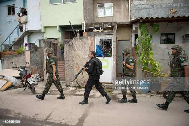 PM paramilitary police BOPE special unit personnel mantain security for Brazilian soldiers conducting a search for weapons in the Favela da Mare slum...