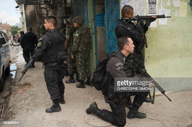 PM paramilitary police BOPE special unit personnel secure the area as Brazilian soldiers search for weapons in the Favela da Mare slum complex in the...