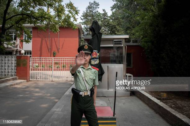A paramilitary police officer gestures outside the Belgium embassy in Beijing on June 19 2019 A Belgian diplomat was expected to travel to China's...