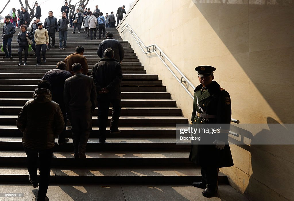 A paramilitary police officer, right, stands guard as people ascend steps in an underpass at Tiananmen Square in Beijing, China, on Thursday, March 14, 2013. Xi Jinping was named China's president by the national legislature, replacing Hu Jintao in the country's most rapid formal transfer of power in more than a generation. Photographer: Tomohiro Ohsumi/Bloomberg via Getty Images