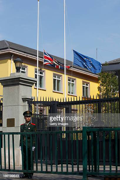Paramilitary police officer stands guard as the British Union Jack flag flies at half-mast at British Embassy on April 09, 2013 in Beijing, China....