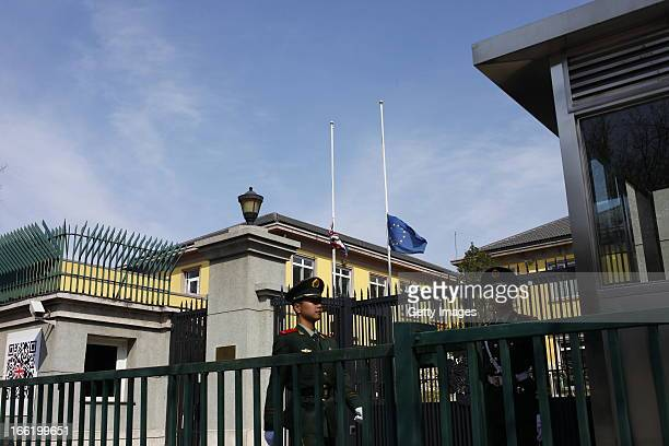 A paramilitary police officer stands guard as the British Union Jack flag flies at halfmast at British Embassy on April 09 2013 in Beijing China...