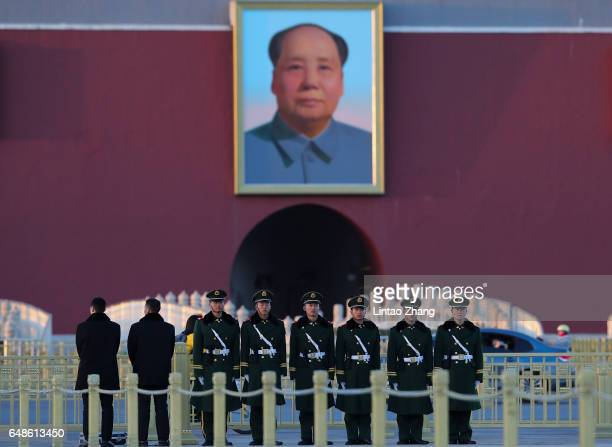 Paramilitary police officer stands guard in front of a portrait of late communist leader Mao Zedong at Tiananmen Square on March 6 2017 in Beijing...