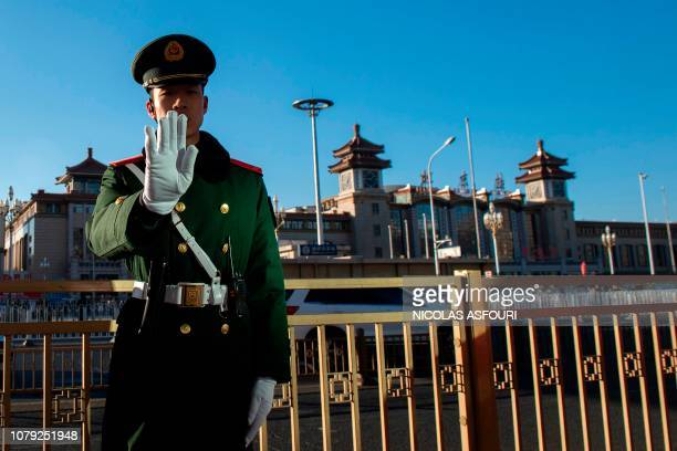 TOPSHOT A paramilitary police officer stands guard outside the Beijing Railway Station in Beijing on January 8 where the private train of North...