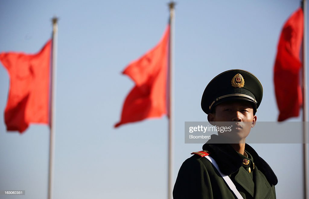 A paramilitary police officer stands guards in front of flags at Tiananmen Square in Beijing, China, on Monday, March 4, 2013. Premier Wen Jiabao will this week formally announce this year's economic targets when he delivers his final work report to the National People's Congress, which begins on March 5. Photographer: Tomohiro Ohsumi/Bloomberg via Getty Images