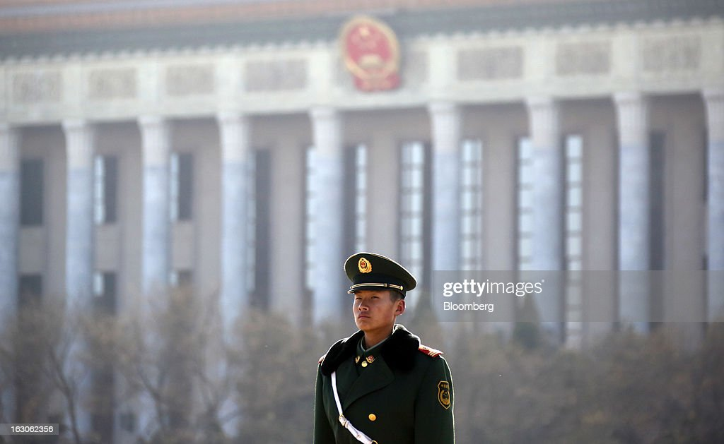 A paramilitary police officer stands guards in front of the Great Hall of the People in Beijing, China, on Sunday, March 3, 2013. Premier Wen Jiabao will this week formally announce this year's economic targets when he delivers his final work report to the National People's Congress, which begins on March 5. Photographer: Tomohiro Ohsumi/Bloomberg via Getty Images
