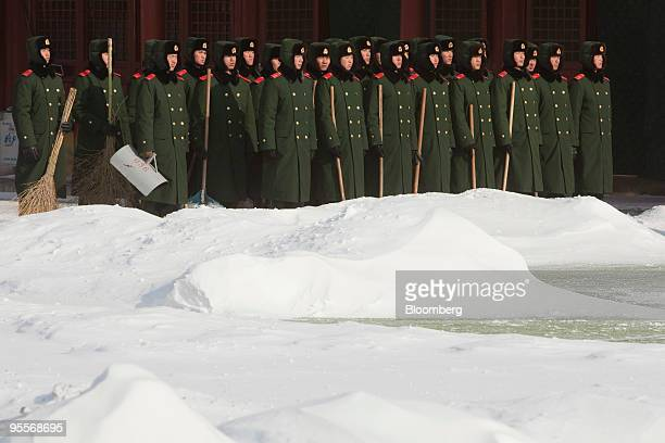 Paramilitary police officers carry snow clearing equipment in Beijing China on Monday Jan 4 2010 Beijing's heaviest snowfall in almost six decades...