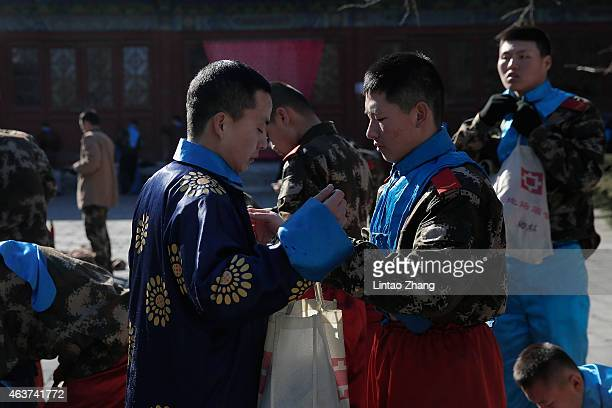 Paramilitary police officers change clothes after performing temple worship ceremony at the Spring Festival Temple Fair for celebrating Chinese Lunar...