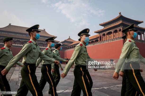 Paramilitary police officers march next to the entrance to the Forbidden City during the opening ceremony of the Chinese People's Political...