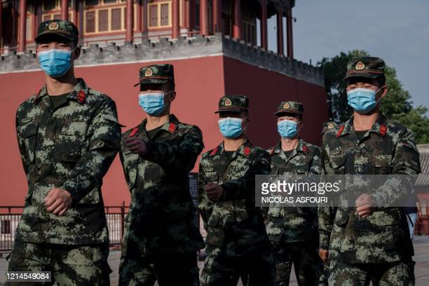 Paramilitary police officers march next to the entrance to the Forbidden City after the opening session of the National People's Congress in Beijing...