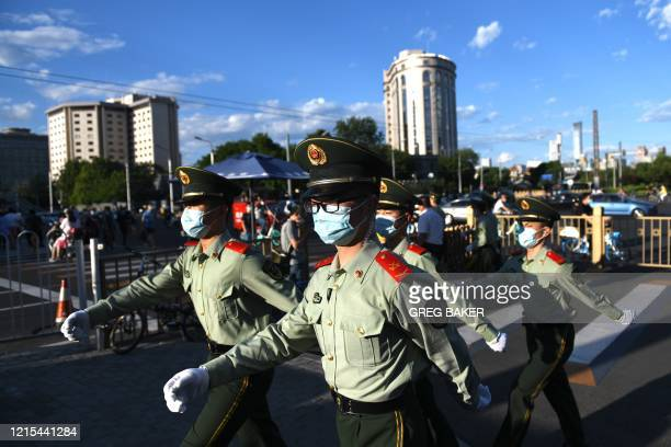 Paramilitary police officers patrol along a street after the closing session of the Chinese People's Political Consultative Conference in Beijing on...
