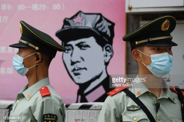 Paramilitary police officers stand guard in front of a poster of late communist leader Mao Zedong on a street south of the Great Hall of the People...