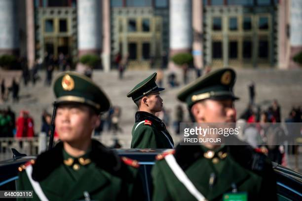 TOPSHOT Paramilitary police officers stand in front of the Great Hall of the People during the opening of the National People's Congress in Beijing...