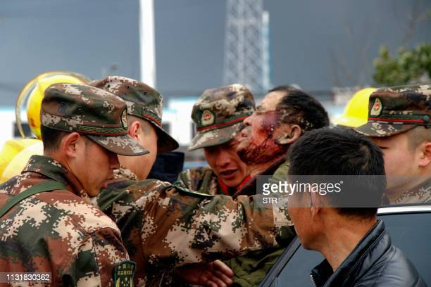 TOPSHOT Paramilitary police officers transfer an injuried man after an explosion in Yancheng in China's eastern Jiangsu province on March 21 2019 A...