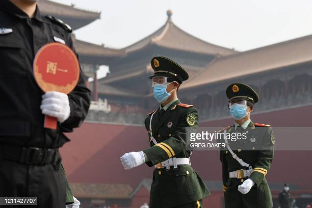 TOPSHOT Paramilitary police officers wear face masks and goggles amid concerns of the COVID19 coronavirus as they march outside the Forbidden City...