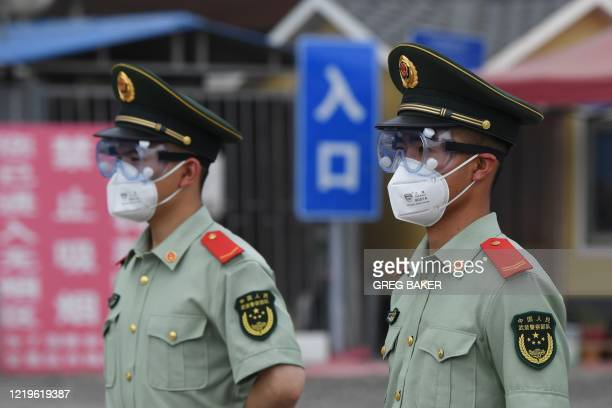 Paramilitary police officers wear face masks and goggles as they stand guard at an entrance to the closed Xinfadi market in Beijing on June 13 2020...
