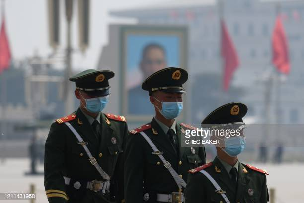Paramilitary police officers wear masks as a preventive measure against the COVID-19 coronavirus as they patrol in Beijing's Tiananmen Square on...