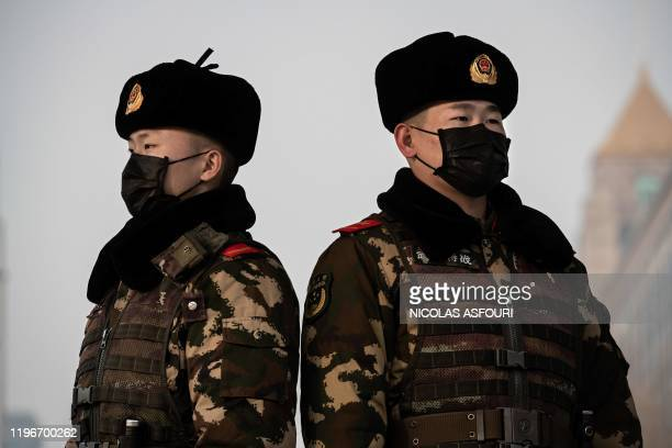 Paramilitary police officers wearing a protective mask to help stop the spread of a deadly virus which began in Wuhan stand guard at the Beijing...