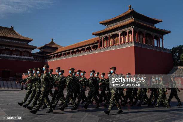 TOPSHOT Paramilitary police officers wearing face masks march in front of the entrance of the Forbidden City in Beijing on May 19 2020 The annual...