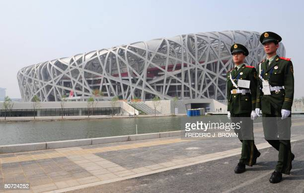 Paramilitary police patrol the exterior of the National Stadium, better known as the Bird's Nest, on April 17, 2008 in Beijing as last-minute...