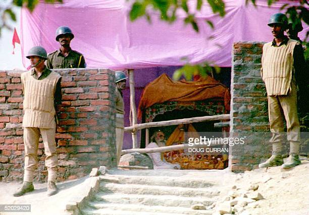 Paramilitary police stand guard around the partially built shrine to Lord Rama as Hindu Priest Acharya Satinder Das prays 09 December 1992 in India...