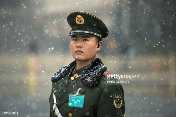 A paramilitary police stands as it snows at the Great Hall of the People where China's President Xi Jinping was elected for a second term during the...