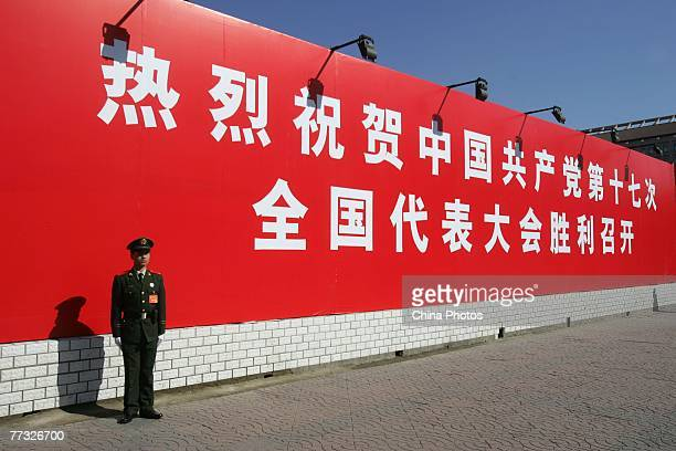 Paramilitary policeman guards in front of a banner marking the opening of 17th National Congress of the Communist Party of China , at the Xidan...
