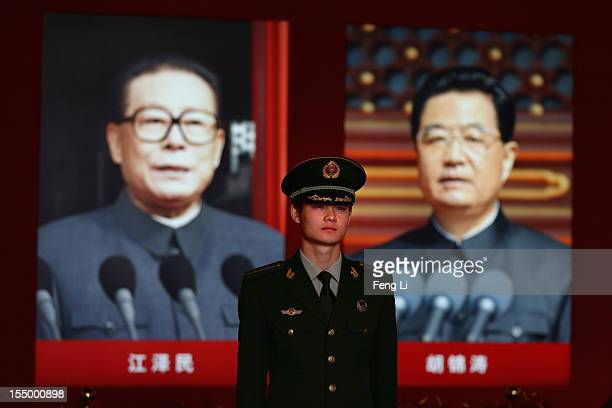 Paramilitary policeman passes the portraits of China's President Hu Jintao and former President Jiang Zeming as visiting an exhibition entitled...