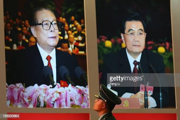 Paramilitary policeman passes the portraits of China's President Hu Jintao and former President Jiang Zeming as visiting an exhibition entitled...