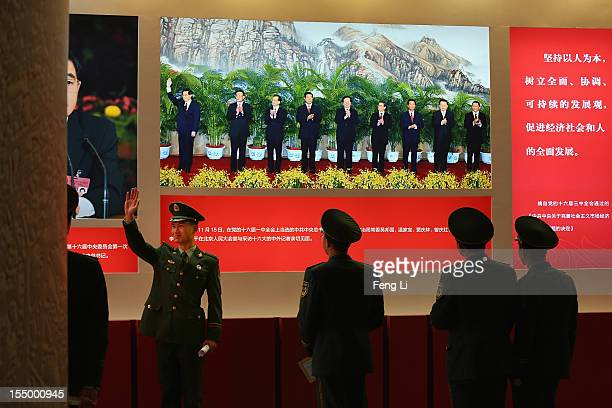 "Paramilitary policeman poses for photo in front of the photo of China's President Hu Jintao as visiting an exhibition entitled ""Scientific..."