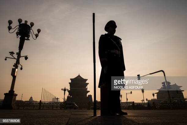 TOPSHOT A paramilitary policeman stands guard ahead of the 7th plenary session of the National People's Congress outside the Great Hall of the People...